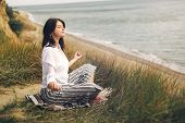 Young Beautiful Woman Relaxing And Practicing Yoga On Beach, Sitting In Grass And Sand, Meditating A poster
