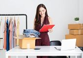 Young Asian Casual Woman Working Small Business Online Packing Jeans To Cardboard Box In Home Office poster