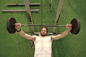 Concentrated On Exercise. Man Athlete Training With Barbell. Athletic Man Pushes Up Heavy Barbell. A poster