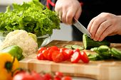 Cook Holds Knife In Hand And Cuts On Cutting Board Green Cucumber For Salad Or Fresh Vegetable Soup  poster