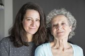Content Elderly Woman And Her Daughter Looking At Camera. Mother And Daughter Portrait With Grey Wal poster