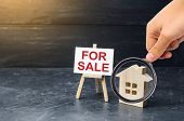Magnifying Glass Is Looking At The Wooden House Stand With A Sign For Sale. Selling A House Or Apart poster
