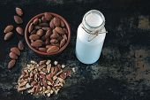 Almond Milk And Raw Almonds In A Bowl On A Stylish Shabby Background. The Concept Of Authenticity Of poster