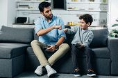 Happy Latin Father Giving Fist Bump To Son After Playing Video Game At Home poster