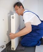 stock photo of assemblage  - plumber installs a heating system  in the bathroom - JPG