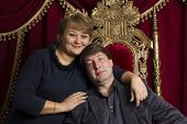 Husband And Wife In A Beautiful Chair. Husband Is King Wife Queen. Middle Aged Couple poster