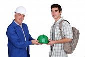 stock photo of jumpsuits  - young apprentice and  mature workmate in jumpsuit - JPG