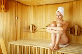 foto of sauna  - The naked girl sits on a bench in a sauna - JPG