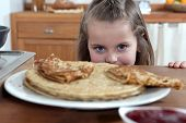 stock photo of greedy  - Greedy girl looking at pancakes - JPG