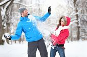 Carefree happy young couple having fun together in snow in winter woodland throwing snowballs at eac