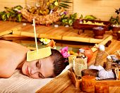 pic of ear candle  - Woman getting massage with ear candle in bamboo spa - JPG