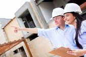picture of real-estate-team  - Civil engineers working in a construction site and pointing away - JPG