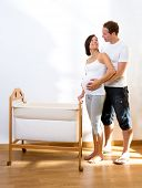 foto of bassinet  - Couple with pregnant woman hug with baby cradle at home - JPG
