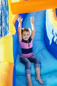 stock photo of yellow castle  - Little Girl sliding down an inflatable Slide - JPG