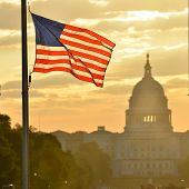 stock photo of democracy  - United States Capitol building silhouette and US flag at sunrise  - JPG