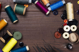 stock photo of rayon  - threads buttons and needles on the brown wooden table - JPG