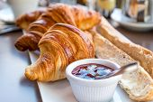 stock photo of bread rolls  - Breakfast with coffee and croissants in a basket on table - JPG