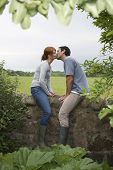 Full length side view of a couple kissing on countryside wall against landscape