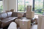 View of packed cardboard boxes in living room of a new home