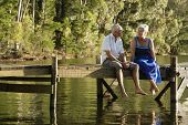 stock photo of pier a lake  - Full length of happy senior couple sitting on pier at lake - JPG