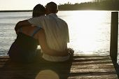 stock photo of pier a lake  - Rear view of happy senior couple sitting on edge of pier by lake - JPG