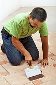 Construction Worker Testing The Joint Color On Ceramic Tiles Floor