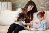 foto of babysitter  - Pretty young babysitter looking after a puppy and a little girl - JPG