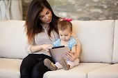 stock photo of babysitter  - Pretty Hispanic babysitter using a tablet computer with a little girl - JPG