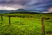 image of cade  - Fence in a field and low clouds over mountains at Cade - JPG