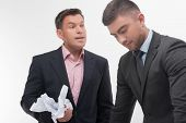 stock photo of angry  - Senior and junior business people in elegant suits. Boss angry with employee looking down, holding crumpled paper isolated on white ** Note: Shallow depth of field - JPG