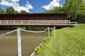 stock photo of covered bridge  - A red covered covered bridge spanning a river - JPG