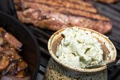 image of cheese-steak  - close up of Home made crock of blue cheese steak butter with steaks on the grill in the background - JPG