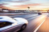 pic of speeding car  - Car driving on freeway at sunset - JPG