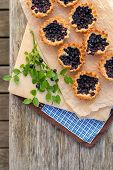 image of pie  - Eight small and fresh blueberry pies on wooden table from top - JPG