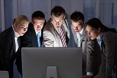 foto of late 20s  - Surprised young business people looking at computer monitor in office - JPG
