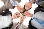pic of huddle  - Low angle portrait of confident business team making huddle against white background - JPG