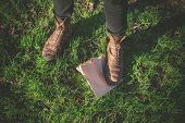 stock photo of stomp  - A foot is standing on a paper bag on the grass - JPG
