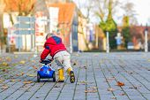 foto of jacket  - Funny cute child in red jacket driving blue toy car and having fun outdoors - JPG