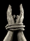 picture of smuggling  - white man hands wrapped with rope around wrists in captivity victim abused slave of work respect for human rights and exploitation concept isolated on black background - JPG
