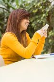 stock photo of canteen  - Beautiful female college student text messaging in outdoor canteen - JPG