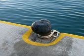 picture of bollard  - Black old bollard with ropes at marina - JPG