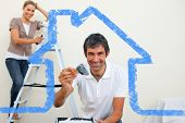 stock photo of wall painting  - Smiling couple painting a wall against house outline - JPG