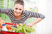 stock photo of supermarket  - Attractive young woman smiling and pushing a cart at supermarket - JPG