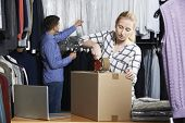 stock photo of dispatch  - Couple Running Online Clothing Store Packing Goods For Dispatch - JPG