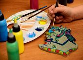 picture of paint palette  - Girl paints a clay toy on the background palette with paints and bubbles - JPG