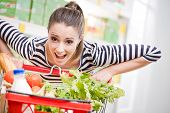 picture of supermarket  - Woman gasping and pushing a full shopping cart at supermarket - JPG