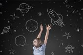 stock photo of boys night out  - Little boy reaching for rocket in drawn space - JPG