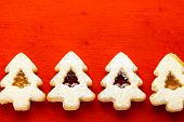 foto of linzer  - Linzer cookies in shape of Christmas tree on red background - JPG