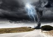 stock photo of doomsday  - Powerful tornado and lightning above countryside road - JPG