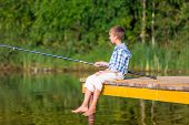 stock photo of rod  - Boy in blue shirt sit on a pier with a fishing rod by the sea - JPG